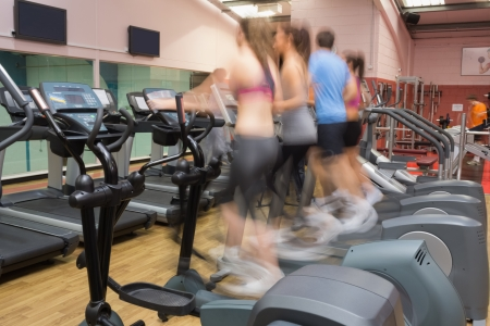 People working out on on step machines at speed in gym photo