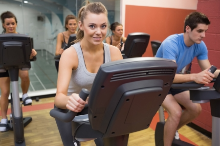 aerobics class: Smiling woman in spin class with others in gym