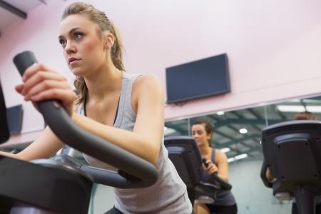 ejercicio aer�bico: Mujer de formaci�n en bicicleta de ejercicio en una clase de spinning en el gimnasio