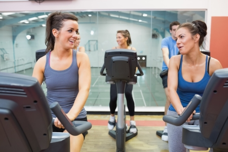 Two women talking while training in a spinning class in gym photo