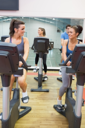 Women talking while training on exercise bike in gym photo