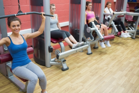 Four women training on weight machines in gym photo