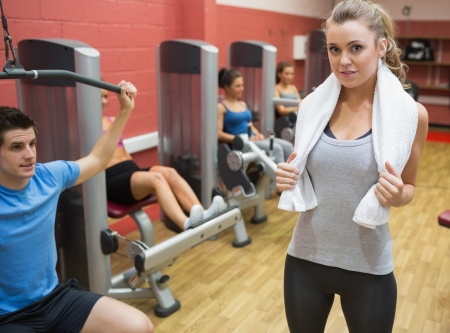 lifting weights: Female trainer teaching her fitness class in weights room in gym