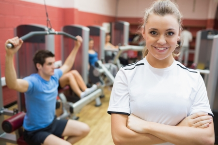 Female trainer smiling in front of class in weights room in gym photo