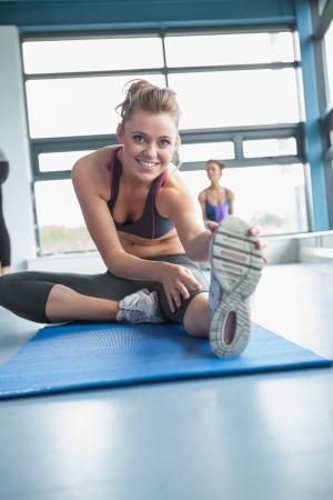 wellness background: Blonde stretching her legs in gym