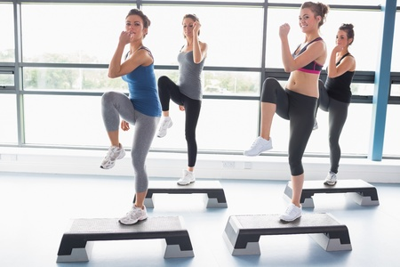 step fitness: For women raising their leg swhile doing aerobics in gym