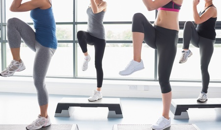 Women raising their legs while doing aerobics in gym photo