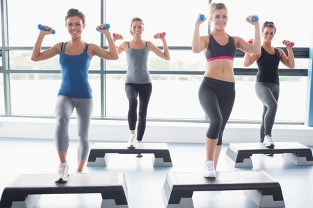 Four women lifting weights while doing aerobics in gym photo