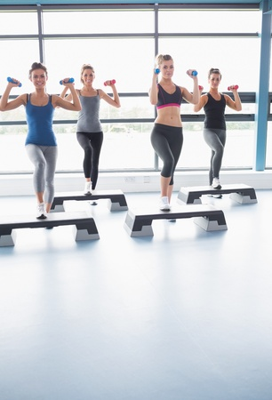 step fitness: Smiling women lifting weights while doing aerobics in gym