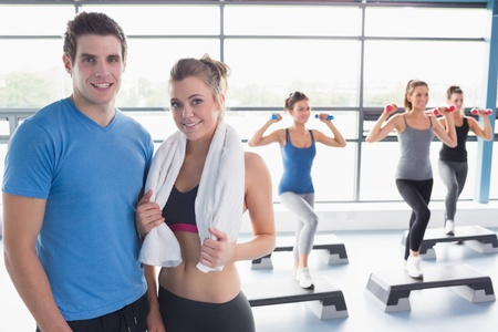 step: Woman and trainer smiling togteher in front of aerobics class in gym Stock Photo