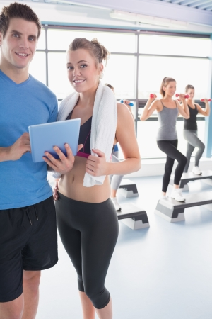 Woman and trainer looking at timetable in aerobics class in gym photo