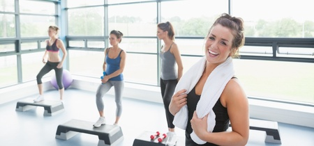 Happy woman taking break at aerobics class in gym photo