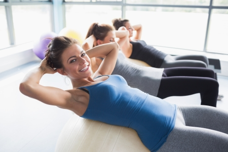 muscle woman: Three women doing sit-ups on exercise balls in gym