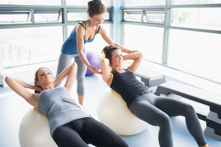 physio: Two women doing sit-ups exercise balls in gym with trainer Stock Photo