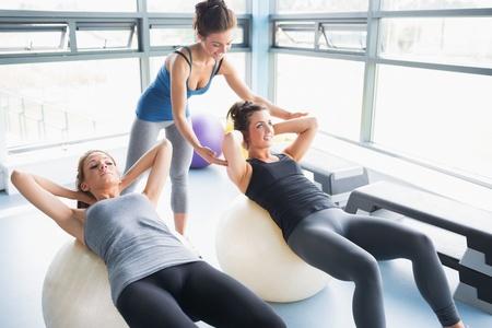 Dos mujeres haciendo abdominales pelotas de ejercicio en el gimnasio con entrenador