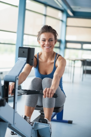 Smiling brunette training on row machine in gym photo