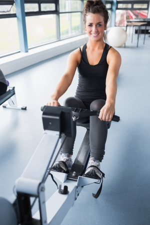 Happy brunette training on row machine in gym photo