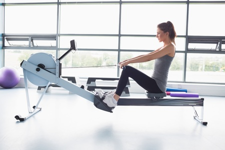 Woman working out on row machine in gym photo