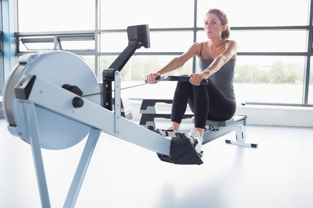 exercise machine: Woman training on row machine in gym