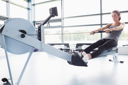 Fit woman training on row machine in gym photo