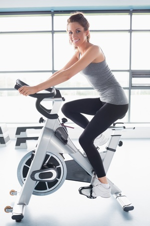 woman bike: Smiling woman training on exercise bike in gym