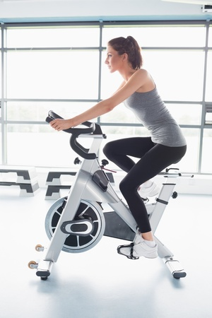 Donna energicamente guida cyclette in palestra