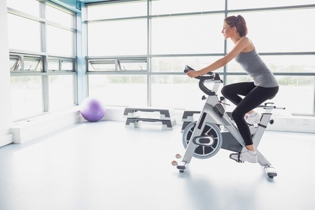 Woman riding an exercise bike in gym photo