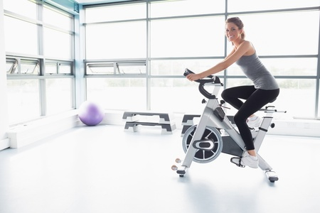 woman sport: Happy woman riding an exercise bike in gym