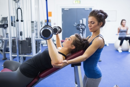 Woman lifting weights and her female trainer photo