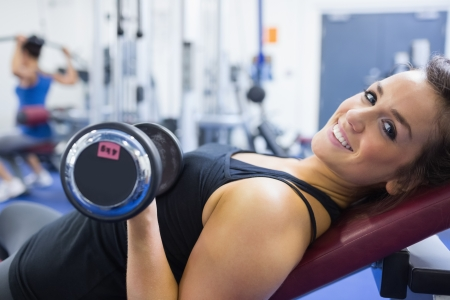 Smiling woman lifting weights in gym photo