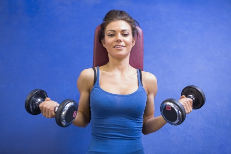 Woman lifting weights while lying down photo