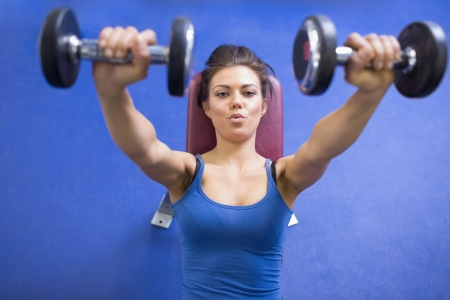 energetically: Black-haired woman energetically lifting weights