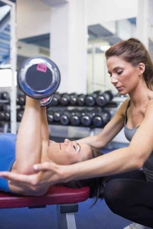 fitness trainer: Concentrated trainer teaching woman lifting weights in gym