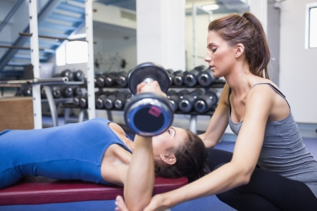 weight machine: Female trainer helping female client lifting weights in gym Stock Photo