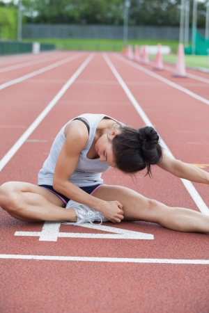 Woman stretching her leg on a track  photo