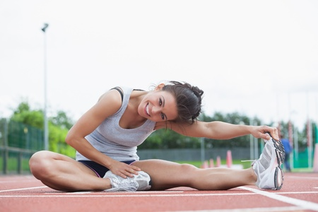 Smiling woman stretching her legs on a track photo
