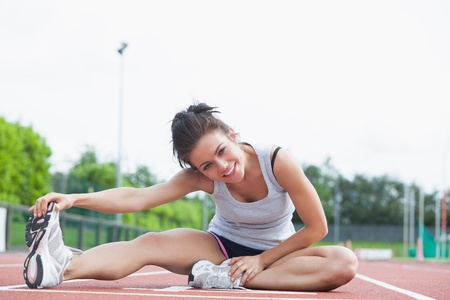 Brunette stretching her legs on on a track photo