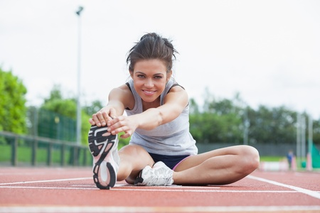 Woman stretching before race on track Stock Photo