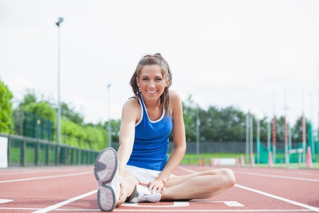 Cheerful woman stretching her leg on a track photo