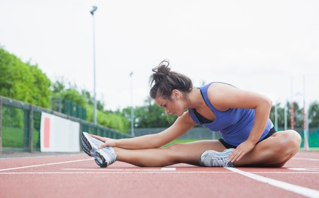 Woman stretching on a track in a stadium Stock Photo - 15583312