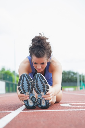 Woman stretching out on a track in a stadium photo