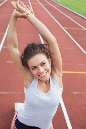 Woman on a track in a stadium stretching her arms photo