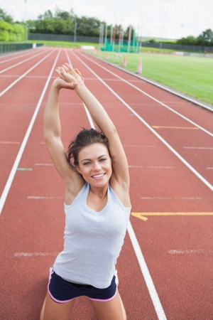 Happy woman stretching her arms on a track Stock Photo - 15592544
