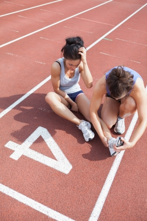 Woman caring about runner with sports injury on running track photo