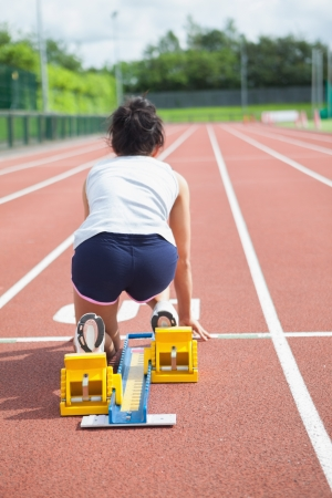 Woman at starting blocks on track field  photo