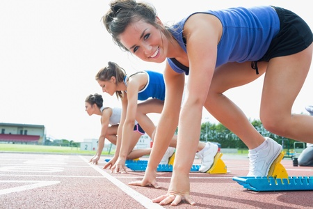 Happy woman at starting blocks on track field Stock Photo