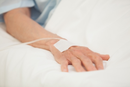 hospitalized: Hand with intravenous drip in hospital bed Stock Photo