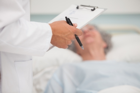 Doctor holding clipboard with elderly lady lying in hospital bed photo