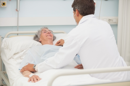 Doctor caring about elderly lady in hospital bed photo