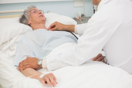 keep watch over: Doctor listening to heartbeat of elderly female patient in hospital bed